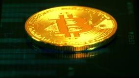 Gouden muntstuk bitcoin, liggend op het scherm met een beeld van de grafiek van citaten, crypto munt Technologie blockchain stock footage