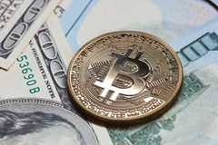 Gouden muntstuk bitcoin op de achtergrond van dollarrekeningen Stock Foto