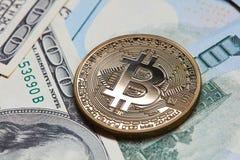 Gouden muntstuk bitcoin op de achtergrond van dollarrekeningen Stock Afbeeldingen