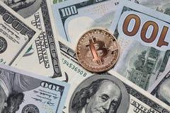 Gouden muntstuk bitcoin op de achtergrond van honderd dollarsrekeningen Stock Afbeelding