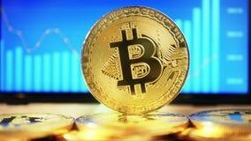 Gouden Muntstuk bitcoin, op de achtergrond van de vertoning met een grafiek van citaten De schuif van de motiecamera stock footage