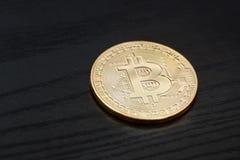 Gouden muntstuk bitcoin op een zwarte houten achtergrond bedrijfsconce Stock Foto