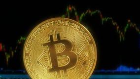 Gouden muntstuk bitcoin, tegen de achtergrond van de vertoning met een grafiek van citaten van crypto-munten Binnen handel Royalty-vrije Stock Fotografie