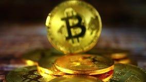 Gouden muntstukken bitkoyn, liggend op de lijst, close-up De schuif van de motiecamera stock footage