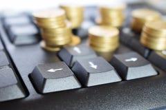 Gouden muntstukken op het toetsenbord, bedrijfsconcept stock fotografie