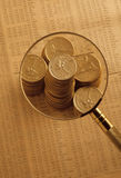 Gouden muntstukken op voorraadindex onder vergrootglas Royalty-vrije Stock Foto's