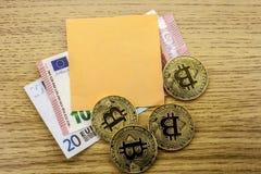 Gouden muntstukken van bitcoin op euro nota's stock afbeelding