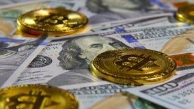 Gouden muntstukken van bitcoins en een achtergrond van honderd-dollar rekeningen Het concept financiële transacties Economie van stock footage