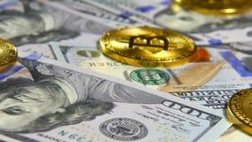 Gouden muntstukken van bitcoins en een achtergrond van honderd-dollar rekeningen Het concept financiële transacties Economie van stock videobeelden