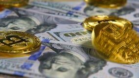 Gouden muntstukken van bitcoins en een achtergrond van honderd-dollar rekeningen Het concept financiële transacties Economie van stock video