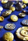 Gouden naaiende knopen op een blauwe achtergrond Royalty-vrije Stock Foto's