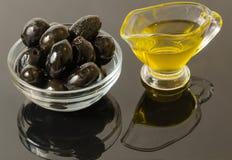 Gouden olijfolie met zwarte olijven Royalty-vrije Stock Afbeeldingen
