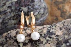 Gouden Oorringen met Diamanten en Parels op natuurstenenbac Royalty-vrije Stock Afbeeldingen