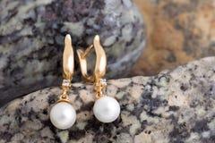 Gouden Oorringen met Diamanten en Parels op natuurstenenbac Royalty-vrije Stock Foto