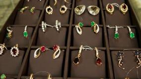 Gouden oorringen met geschotene edelstenenschuif, Gouden die juwelen voor vrouwen, voor verkoop in een juwelenopslag worden bloot stock footage
