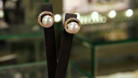 Gouden oorringen met kristallen en parels op een voetstuk, juwelen, klassieke juwelen voor dames in storefront van juwelen stock videobeelden