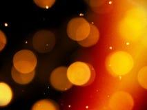Gouden oranje gloed op een zwarte achtergrond met ronde vage lichten en heldere fonkelingen stock afbeeldingen