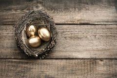 Gouden paaseieren op houten achtergrond Stock Afbeelding