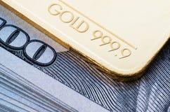 Gouden passement 999 fijnheid 9 tegen de achtergrond van een honderd-dollar factureert royalty-vrije stock foto