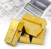 Gouden passementbars die bovenop elkaar met financiële achtergrond worden gestapeld stock foto