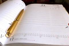 Gouden pen en notitieboekje Stock Afbeeldingen