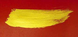 Gouden penseelstreek op rood Royalty-vrije Stock Afbeeldingen