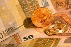 Gouden phisical bitcoin met Euro bankbiljetten Bitcoincryptocurrency stock foto's