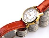 Gouden polshorloge op het toenemen stapel van zilveren muntstukken Stock Fotografie