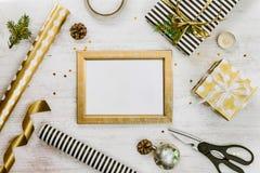 Gouden ptotokader, giftdozen, denneappels en Kerstmisspeelgoed en verpakkingsmaterialen op een witte houten oude achtergrond Kers Royalty-vrije Stock Foto