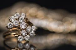 Gouden ring met diamanten op zwarte spiegeloppervlakte Stock Foto