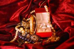 Gouden ring met parel en zirkoon in een doos op een donkerrode achtergrond met parelhalsband en armband Stock Foto