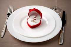 Gouden ring in rood geval op witte plaat met vork, mes en glas Royalty-vrije Stock Afbeeldingen