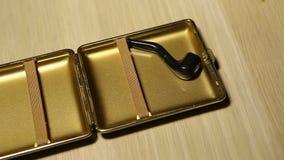 Gouden rokende de pijp houten lijst van het sigaretgeval niemand hd lengte stock footage