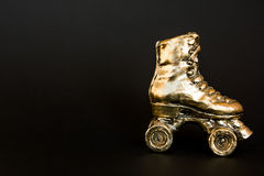 Gouden rolschaats tegen zwarte achtergrond Stock Foto