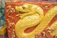 Gouden slangbeeldhouwwerk op muur van het heiligdom Stock Afbeelding