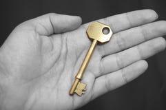 Gouden sleutel in een hand Royalty-vrije Stock Fotografie