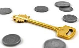 Gouden sleutel en muntstukken Royalty-vrije Stock Foto's