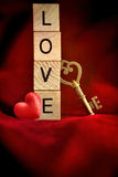 Gouden sleutel met houten brieven die de woordliefde spellen Stock Fotografie