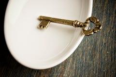 Gouden Sleutel in Schotel Stock Fotografie