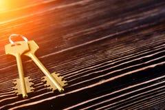 Gouden sleutels tot de flat op houten achtergrond met copyspace stock foto