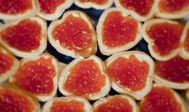 Gouden smothtrouwringen op sandwiches met kaviaar Royalty-vrije Stock Fotografie