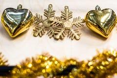 Gouden sneeuwvlokken en harten op lichte achtergrond Royalty-vrije Stock Foto