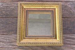 Gouden spiegel met barok kader op houten achtergrond Royalty-vrije Stock Fotografie