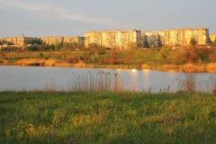 Gouden stad en groene weide bij de rivier Royalty-vrije Stock Afbeelding