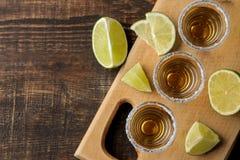Gouden tequila in een glas schoot glas met zout en kalk op een bruine houten achtergrond Hoogste mening met ruimte voor tekst royalty-vrije stock foto's