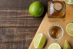 Gouden tequila in een glas schoot glas met zout en kalk op een bruine houten achtergrond Hoogste mening met ruimte voor tekst stock afbeeldingen