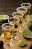 Gouden tequila in een glas schoot glas met zout en kalk op een bruine houten achtergrond Staaf Alcoholische dranken stock afbeelding