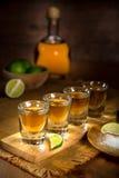 Gouden Tequila geschotene die glazen en fles in een groeps artistieke verlichting worden gediend stock afbeelding