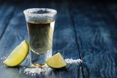 Gouden tequila in glas/glas- met zout en kalk dichte omhooggaand op blauwe houten achtergrond Staaf Alcoholische dranken Plaats v stock foto