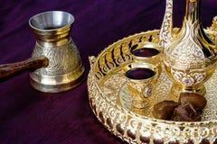 Gouden Traditionele Arabische die koffie met dallah, jezva van de koffiepot, kop en data wordt geplaatst Donkere achtergrond stock foto's
